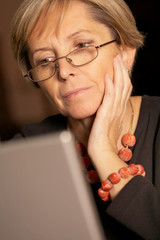 Attractive mature woman using laptop