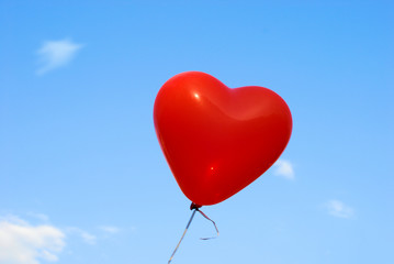 Red heart-shaped ballon with blue sky