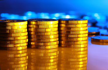 Stacks of coins, in tones of gold and blue, reflected.