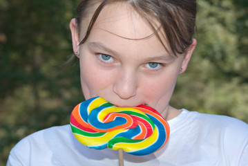 a teenage girl has a big swirly lollipop