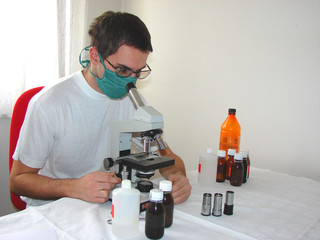 Young doctor with mask and microscope