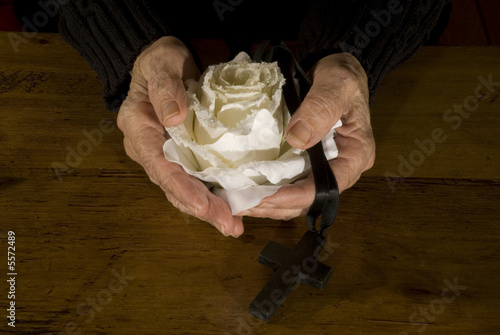 old hands with white rose and black cross