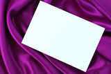 Blank white card on purple and magenta colored satin cloth. poster