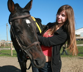 Long-haired female model with black horse close-up portrait