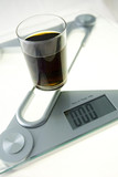 "Glass of ""diet cola"" on the electronic balance showing zero kg"