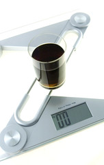 Glass of diet cola on the electronic balance showing zero kg
