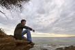 jeune homme assis seul face à la mer solitude tristesse