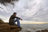 jeune homme assis seul face à la mer solitude tristesse poster
