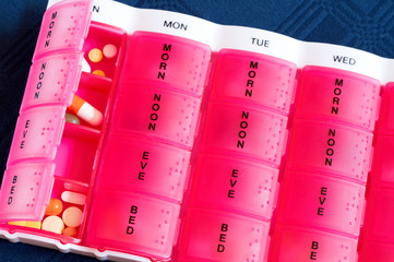 Medical colorful pills in the pink box for daily use