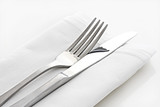 Silver knife and fork on white linen napkin. poster