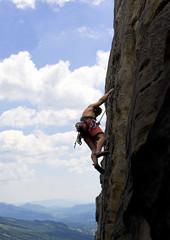 Climber on a vertical rock, high above valley