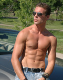 A shirtless man sitting on the hood of a sports car poster