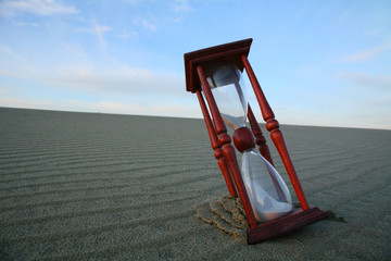 Hourglass on the evening dune and wavy lines of sand.