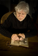 old lady reading in bible with magnify glass