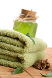 Green towels and liquid soap in glass jar poster