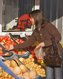 Image of a woman buying fruits in a market. poster