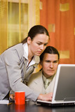 Business couple working on laptop computer in office poster