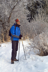 Man snowshoer in winter mountain forest