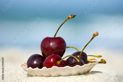 Cherries in a seashell on the beach. Summer concept