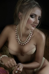 Blond woman in beige push-up corset and pink necklace