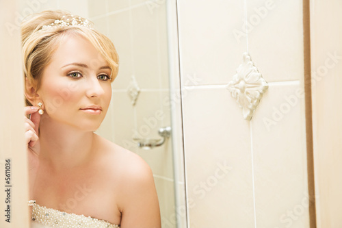 Beautiful blond bride in pearl  dress in front of mirror