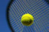 Tennis racket hitting ball against blue sky poster