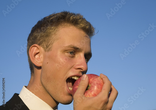 Young business man in suit eating a fresh red apple.