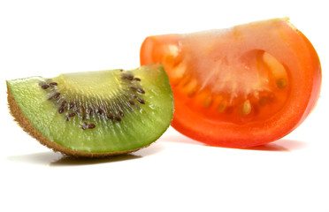 kiwi and a tomato on white. Isolation, shallow DOF.