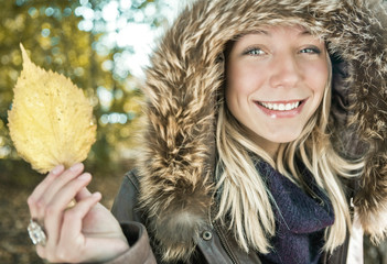 Blond girl holding yellow leaf