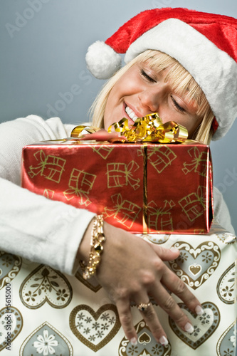 BLond Swedish girl in santa hat holding christmas presents