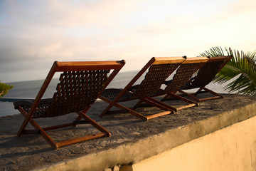 three deck chairs next to the swimming pool facing the ocean.