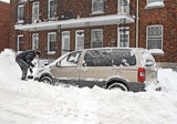 Man shovelling and removing snow from his car. poster