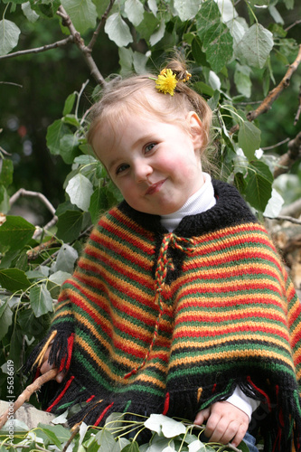 Smiley little girl sit on tree branch