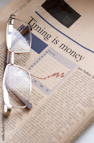 Business section of newspaper and glasses