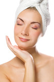 Young lovely lady applying moisturizer to her face  poster