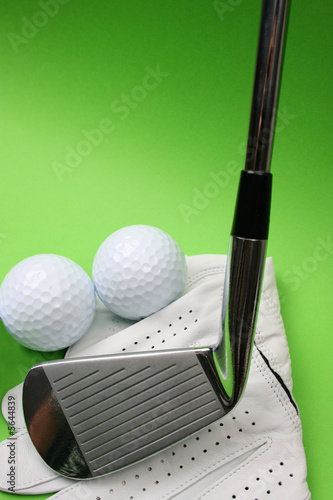 Golf glove, club and balls on a green background
