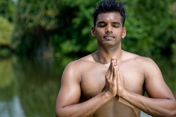 A well-built Asian man practising yoga outside by water