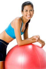 An attractive young Asian woman resting on fitball