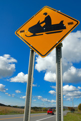 roadside snow scooter warning sign against blue sky