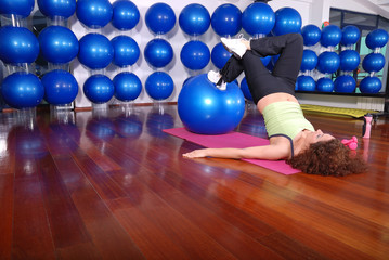 young woman exercising with pilates ball