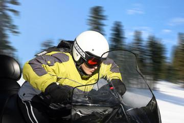 A young man riding a snowmobile