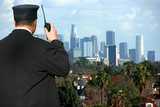 Security agent watching Los Angeles from hilltop poster