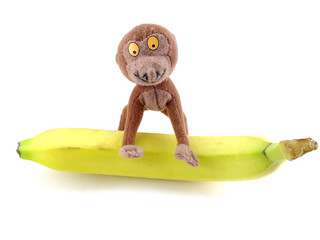funny toy monkey sitting on a banana. Isolated