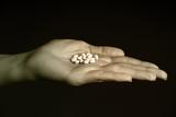 Female hand holding white generic pills poster