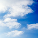 The blue sky is covered by white fluffy clouds. poster