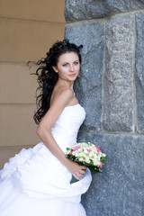 a beatiful bride by the stone wall