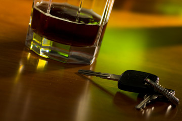 A set of car keys and glass of beer on a bartable.