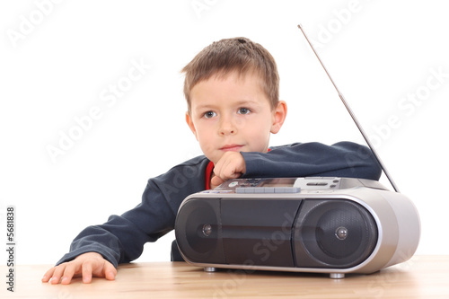 cute 6 years old boy listening to music isolated on white