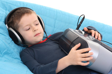 cute 6 years old boy listening to music on the sofa