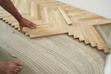 Carpenter on work putting wood floor - parquet pieces poster